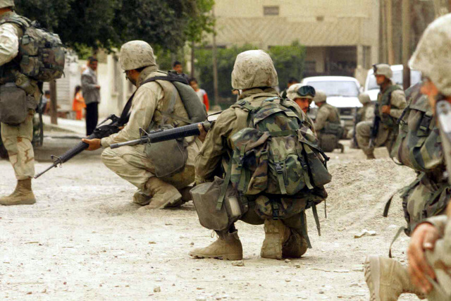 Armed with Colt 5.56mm M16A2 Assault Rifles, US Marine Corps (USMC) personnel with the 3rd Battalion, 7th Marines and Charlie Company, 1ST Tank Battalion, 7th Marines pause on a security patrol in Baghdad, Iraq, during Operation IRAQI FREEDOM