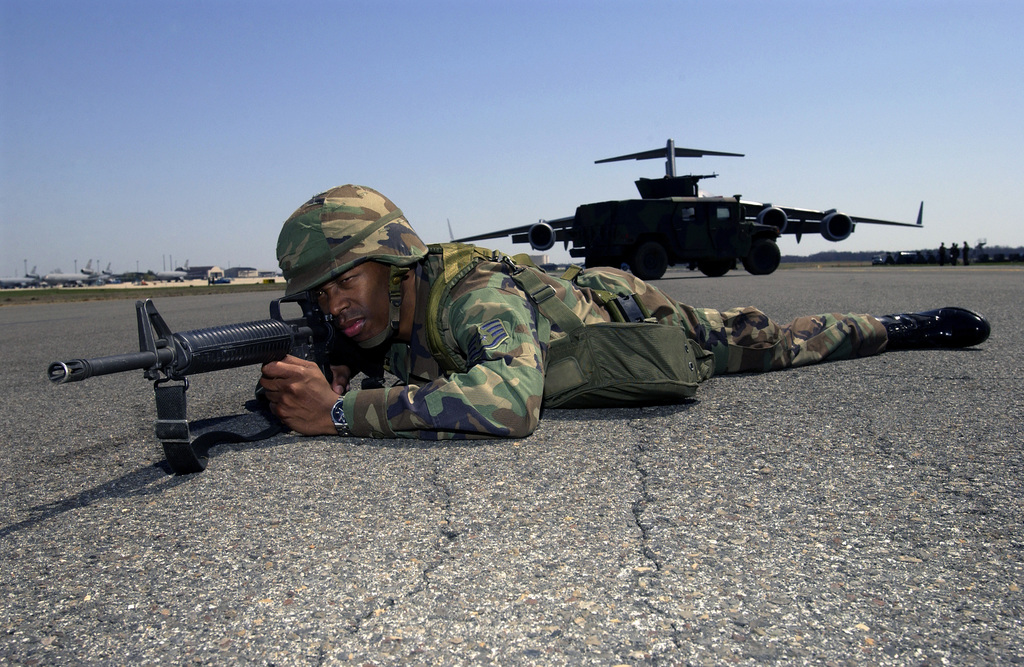US Air Force (USAF) STAFF Sergeant (SSGT) Jacob Thompson, 305th Civil Engineer Squadron (CES), McGuire Air Force Base (AFB), New Jersey (NJ), with a 5.56 mm M16A2 rifle, assumes a defensive position near a C-17A Globemaster III during NUCLEAR SURETY SUPPORT Exercise (M999). The exercise responds to a scenario where a disgruntled aircrew crewmember seizes control of an aircraft and a nuclear weapon, threatening to shoot the crew and explode the weapon. A High-Mobility Multipurpose Wheeled Vehicle (HMMWV) with a weapon turret blocks the C-17A