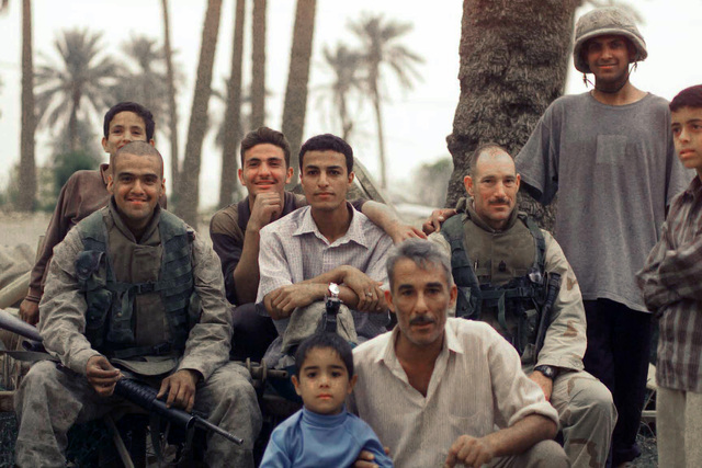 US Marine Corps (USMC) personnel with the 3rd Battalion, 7th Marines sit and have their picture taken next to Iraqi children during a break while on a security patrol in Baghdad, Iraq, during Operation IRAQI FREEDOM