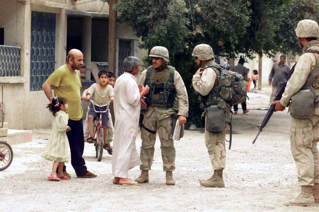 US Marine Corps (USMC) Sergeant Major (SGM) Rick Lamelin, from Stafford Springs, Connecticut, with the 3rd Battalion, 7th Marines talks with Iraqi civilians while on a security patrol in Baghdad, Iraq, in support of Operation IRAQI FREEDOM