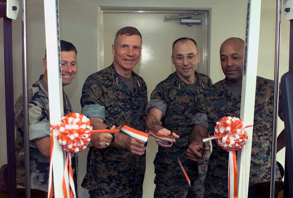 """Colel (COL) Drew Bennett (left), General (GEN) Michael W. Hagee, (left center), Commandant of the Marine Corps (CMC), Lieutenant General (LGEN) Wallace C. """"Chip"""" Gregs, (right center), Commanding General, III Marine Expeditiary Force (MEF); Commander, Marine Corps Bases, Japan; Commander, Marine Forces, Japan, and Sergeant Major of the Marine Corps Alford McMichael, (right), """"cut a ribb"""" some weight equipment. The equipment is installed in a lounge area of a designated barracks as part of a theme lounge plan set forth by 3rd Marine Divisi. GEN Hagee visited III Marine Expeditiary Force (MEF) for the first time as the CMC. During his visit he will tour Marine bases located..."""