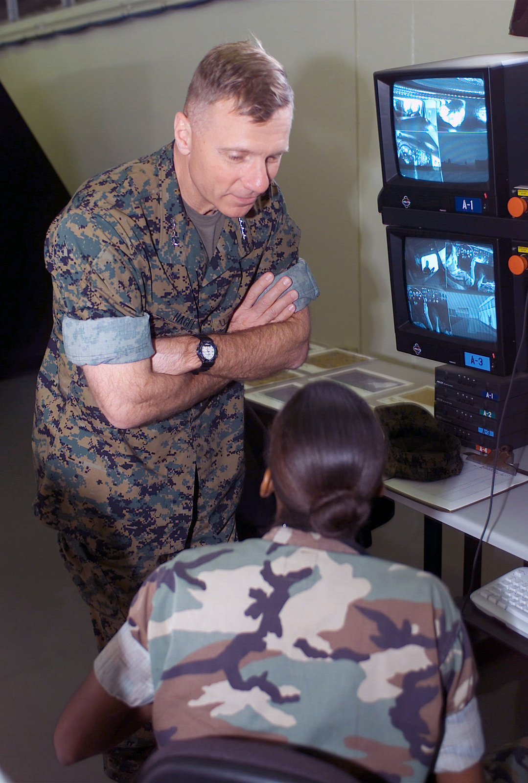 General (GEN) Michael W. Hagee, (right), Commandant of the Marine Corps (CMC), gets briefed by Corporal (CPL) Amina Welch, dispatcher, on the adventures that Marines have while in training in the Medium Tactical Vehicle Replacement-Training System. The simulator trains Marines in a variety of situations encountered driving the Medium Tactical Vehicle Replacement (MTVR) in the Okinawa area. GEN Hagee visited the III Marine Expeditionary Force (MEF) for the first time as the CMC, during his visit he will tour bases located on Okinawa, Japan