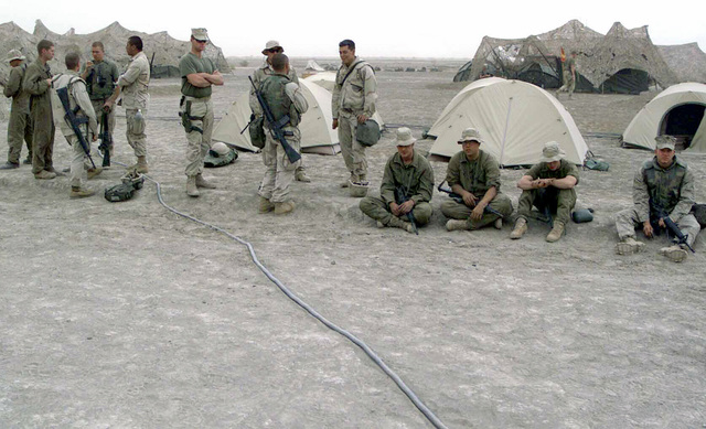 US Marine Corps (USMC) Marines and US Navy (USN) Sailors from the 24th Marine Expeditionary Unit (MEU) Special Operations Capable (SOC) and the Marine Wing Support Squadron 371 (MWSS-171, wait in line to call their loved ones back home, while deployed at Camp Fenway, Iraq, during Operation IRAQI FREEDOM
