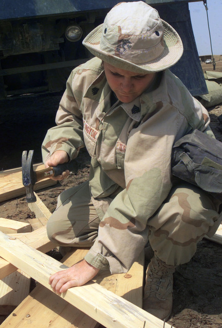 US Marine Corps (USMC) Sergeant (SGT) Marla Pocklington, with an Engineer Detachment, 24th Marine Expeditionary Unit (MEU), Service Support Group 24, hammers out old nails from a board and makes tables and benches for the children in the village of Hasham, Iraq, in support of Operation IRAQI FREEDOM