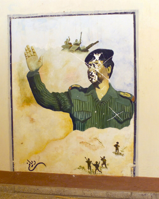A wall art depiction of Saddam Hussein waving, on a Republican Guard base wall, in the vicinity of Daly airfield, Iraq , during Operation IRAQI FREEDOM