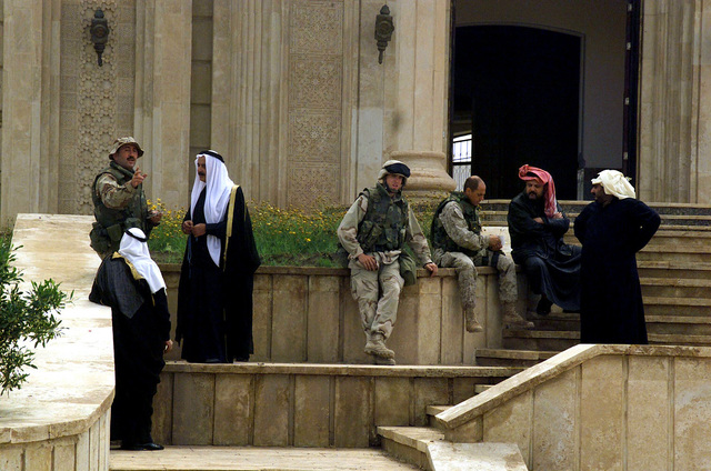 US Marine Corps (USMC) Marines from 1ST Light Armor Reconnaissance Battalion, Highlanders, Camp Pendleton, California (CA), interact with the local Iraqi civilians in front of Saddam's palace located in the town of Tikrit, Saddam's home town. The Marines are providing security in support of Operation IRAQI FREEDOM