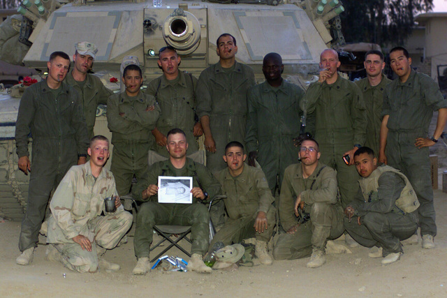 At an assembly area in Baghdad, Iraq, US Marine Corps (USMC) personnel of Charlie Company, 1ST Tank Battalion, 7th Marines smoke cigars to celebrate the birth of Captain (CAPT) Jano Carlsons son, during Operation IRAQI FREEDOM