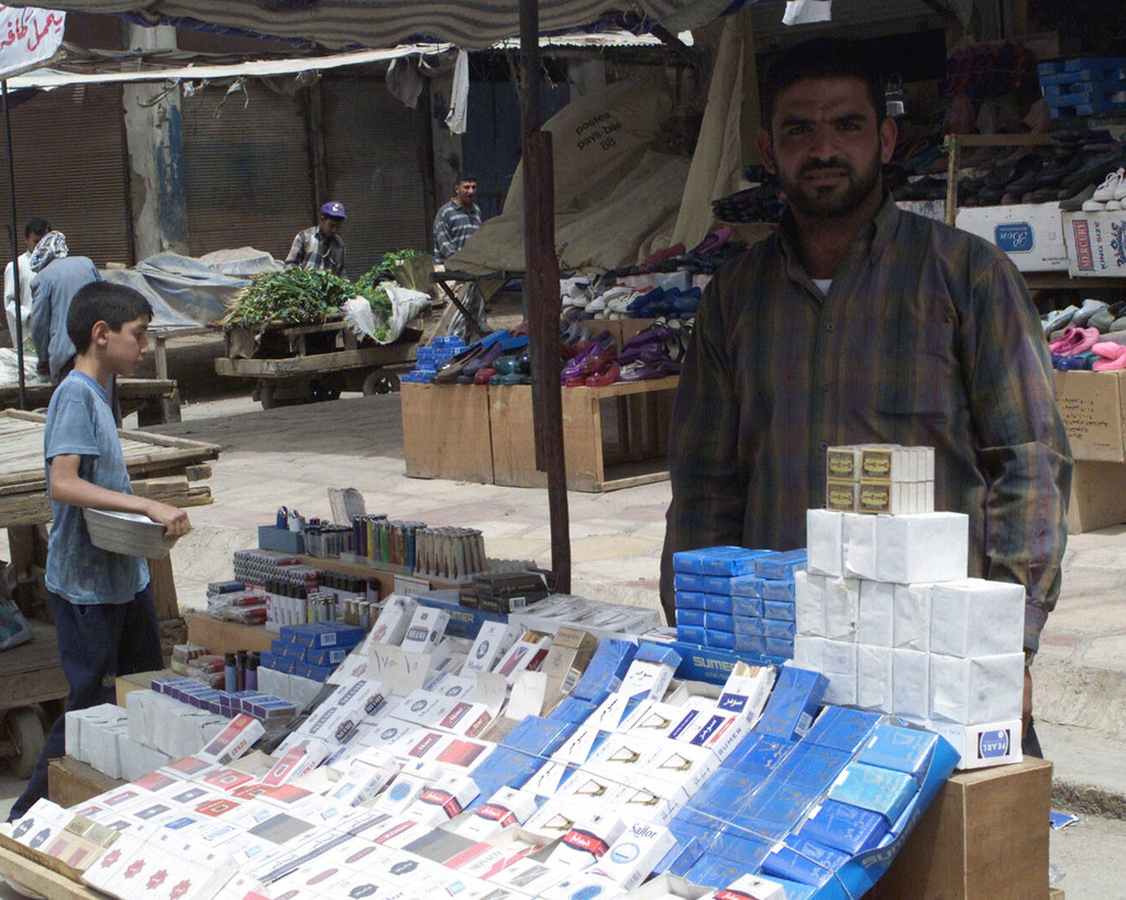 An Iraqi cigarette vendor in the Al Nu'maniyah, Iraq, market place selling his wares, during Operation IRAQI FREEDOM