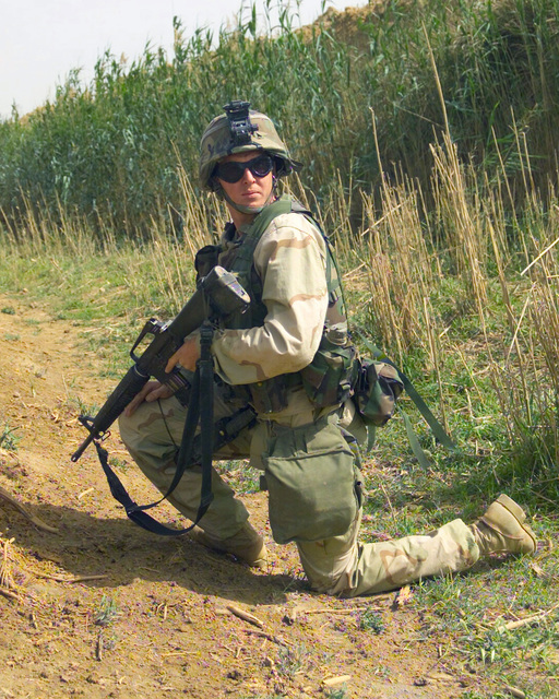 Armed with a Colt 5.56mm M16A2 rifle, US Marine Corps (USMC) Private First Class (PFC) James S. Creel of Golf Company, 2nd Battalion, 6th Marines, on a security patrol in the vicinity of Daly airfield, Iraq, during Operation IRAQI FREEDOM