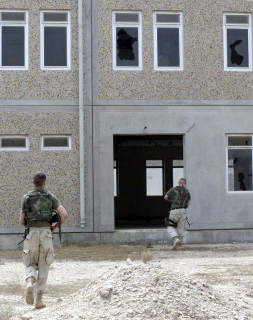 US Marine Corps (USMC) Captain (CAPT) Dana Makjewicz, an Infantry Officer (IO) with the 1ST Marine Expeditionary Force (MEF), leads Corporal (CPL) Christopher Lamont, an Intelligence SPECIALIST through a former Turkish military base outside of Three Rivers, Iraq, during Operation IRAQI FREEDOM