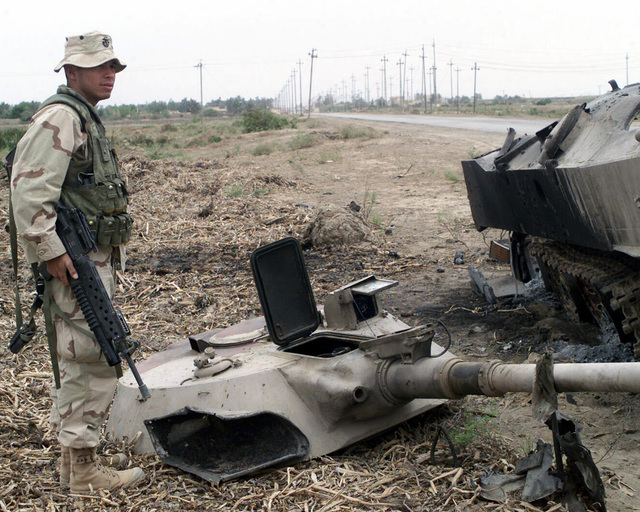 US Marine Corps (USMC) Sergeant (SGT) Saul Cardenas, an Infantry Rifleman attached to the 1ST Intelligence Battalion (IB), 1ST Marine Expeditionary Force (MEF) stands next to a destroyed Iraqi BMT-2 Infantry Fighting Vehicle (IFV), in Al Nu'maniayh, Iraq, in support of Operation IRAQI FREEDOM