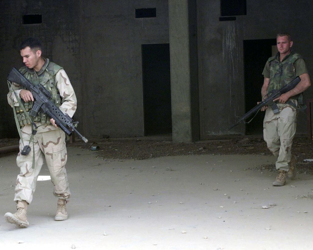 US Marine Corps (USMC) Sergeant (SGT) Saul Cardenas, left, an Infantry Riflemen attached to 1ST Intelligence Battalion (IB), 1ST Marine Expeditionary Force (MEF) and Corporal (CPL) Brian Lipp, an MEF Radio Operator (RO) scout a former Turkish military base near Three Rivers, Iraq, in support of Operation IRAQI FREEDOM