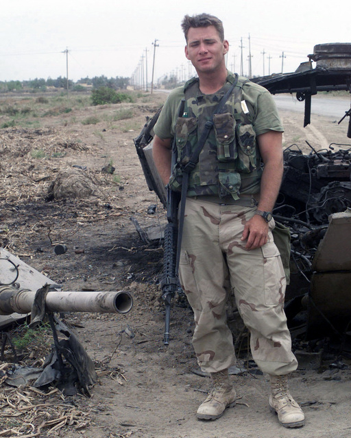 US Marine Corps (USMC) Sergeant (SGT) Timothy Barnes, an Infantry Rifleman attached to the 1ST Intelligence Battalion (IB), 1ST Marine Expeditionary Force (MEF) stands next to a destroyed Iraqi BMT-2 Infantry Fighting Vehicle (IFV), in Al Nu'maniayh, Iraq, in support of Operation IRAQI FREEDOM