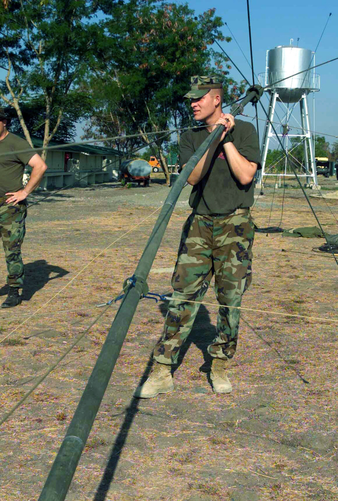 US Marine Corps (USMC) Computer SPECIALIST Lance Corporal (LCPL) Mike C. Hill, with the 2nd Battalion, 7th Marines, prepares to lift the top of an antenna for communications during Exercise BALIKATAN 2003
