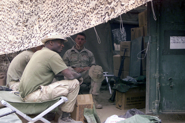 US Marine Corps (USMC) Marines assigned to S-4 Logistics, Command Element, 24th Marine Expeditionary Unit (MEU) Special Operations Capable (SOC), sit under a camouflaged tent at Camp Fenway, Iraq, during Operation IRAQI FREEDOM