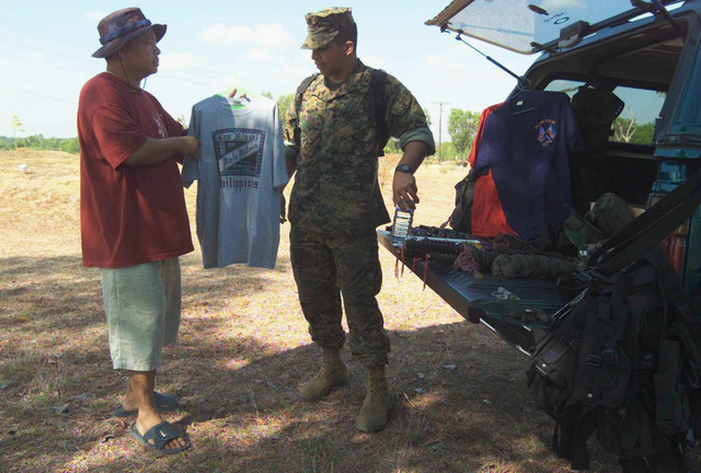 US Marine Corps (USMC) Rifleman Corporal (CPL) Gabriel Morales, with the 2nd Battalion, 7th Marines, bargains for a better price on a shirt with Mr. Nelson Quiddam, during Exercise BALIKATAN 2003