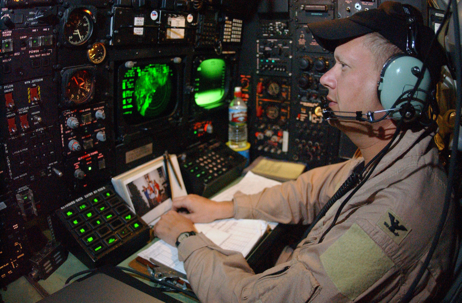 US Air Force (USAF) Colonel (COL) George Gagnon, Navigator, 40th Expeditionary Bomb Squadron (EBS), checks his instruments while listening to radio communications during a USAF B-52 Stratofortress close air support mission (CAS) over Iraq, during Operation IRAQI FREEDOM