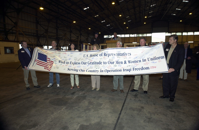A Congressional delegation led by Speaker of the House J. Dennis Hastert (at podium) unrolls a banner signed by the US House of Representatives in support of the military men and women's efforts during Operation IRAQI FREEDOM. The delegation made the visit to the forward-deployed location in time to see some of the last B-52 Stratofortress (not shown) aircraft leaving to return home