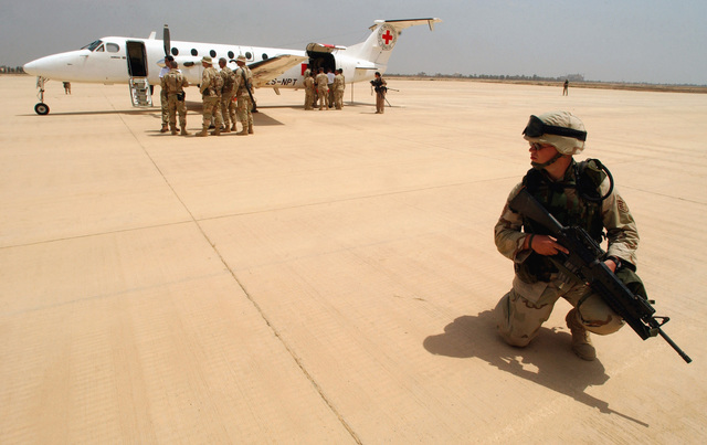 A US Air Force Security Police (SP) armed with a 5.56mm M16A2 rifle provides airfield security for a International Red Cross (IRC) Beechcraft 1900 Executive-Liner aircraft, as supplies are offloaded at Baghdad International Airport (BIAP), during Operation IRAQI FREEDOM. The IRC aircraft is the first civilian aircraft that landed on the commercial runway sense the start of the Operation