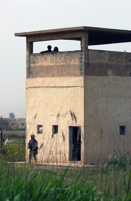 US Air Force (USAF) and US Army (USA) personnel secure a watchtower during a perimeter check at an abandoned Iraqi Air Base (AB) while conducting a sight-survey of the base during Operation IRAQI FREEDOM