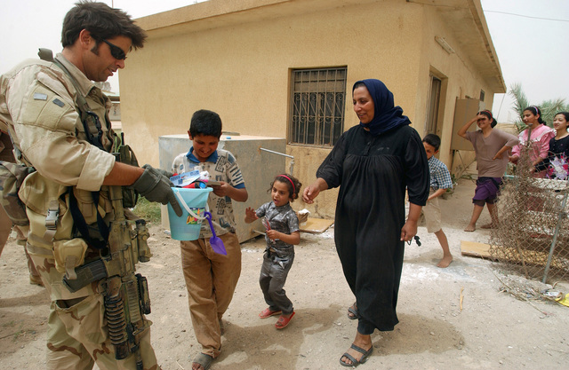 US Air Force (USAF) STAFF Sergeant (SSGT) David Overton, Combat Control Team (CCT), 23rd Special Tactics Squadron (STS), Hurlbert Air Force Base (AFB), Florida (FL), passes out candy and toys to Iraqi children in Baghdad during Operation IRAQI FREEDOM