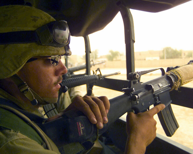 Armed with a Colt 5.56mm M16A2 rifle, a US Marine Corps (USMC) rifleman rides in the cargo bed of a 7-ton truck at Al Hay, Iraq, during Operation IRAQI FREEDOM