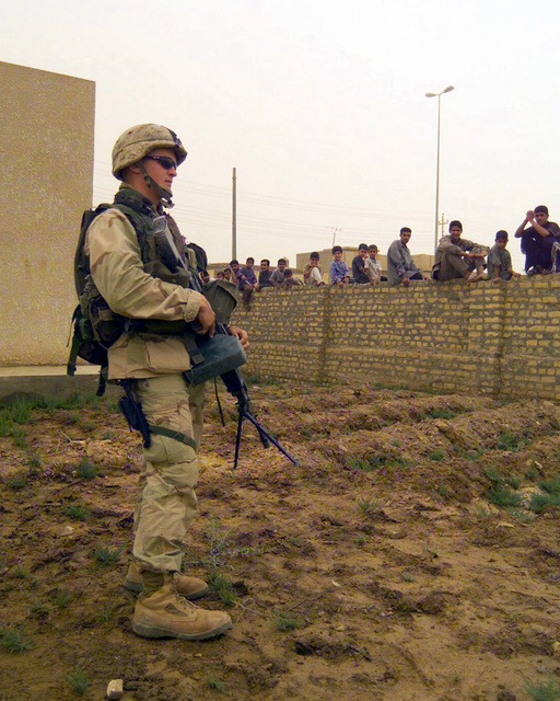 Armed with a Colt 5.56mm M16A2 rifle, a US Marine Corps (USMC) rifleman stands guard outside of a schoolhouse at Al Hay, Iraq, during Operation IRAQI FREEDOM