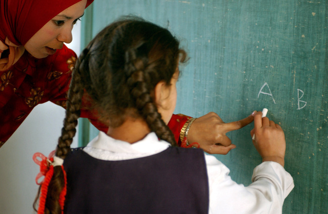 Sahar, an Iraqi schoolteacher at the school in Abu Grahib, Iraq, helps a girl write the alphabet on the chalkboard, during opening day of classes. The school had been closed down since the start of Operation IRAQI FREEDOM