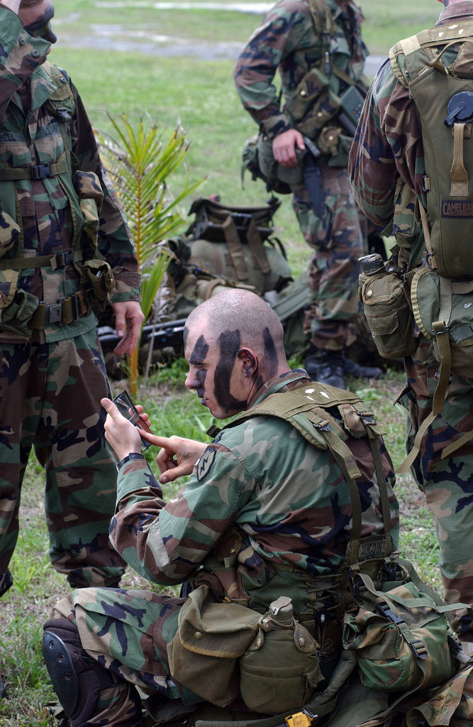 US Army (USA) Soldiers from the 2nd Battalion, 27th Infantry Regiment (2/27) Charlie Company, 25th Infantry Division (ID) [Light], Schofield Barracks, Hawaii (HI), apply camouflage before being picked as part of an Airborne Insert on an island during Exercise TANDEM THRUST 2003
