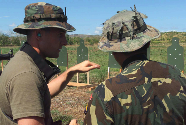 US Marine Corps (USMC) Reconnaissance Marine Corporal (CPL) Michael J. Wing, left, with 3rd Reconnaissance Battalion, in support of 2nd Battalion, 7th Marines, explains the stationary single target engagement drills to Filipino Army Private First Class (PFC) Aymer Salamanca, during Exercise BALIKATAN 2003