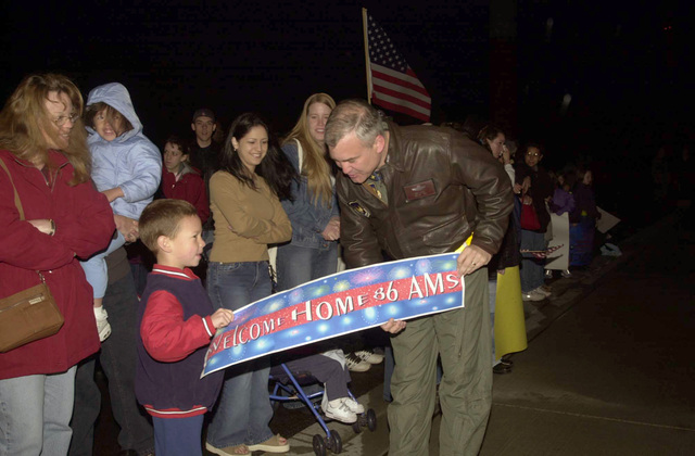 US Air Force (USAF) Brigadier General Erwin F. Lessel III, Commander, 86th Airlift Wing, Ramstein Air Base, Germany, visits with a little boy who made a welcome home sign for his father, a 86th Contingency Response Group (CRG) member, returning from Operation IRAQI FREEDOM