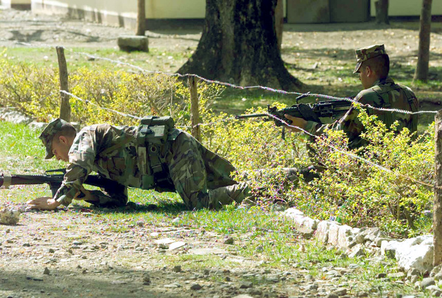 US Marine Corps (USMC) Infantryman Corporal (CPL) Alexander W. Hawley, crawls under barbwire held open by Lance Corporal (LCPL) Juan J. Morales both with the 2nd Battalion, 7th Marines, practicing the Filipino style of patrolling in the jungle, during Exercise BALIKATAN