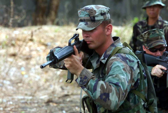 US Marine Corps (USMC) Infantryman Corporal (CPL) Mathew J. Johnston, with the 2nd Battalion, 7th Marines, aims at a simulated enemy using a Colt 5.56mm M16A2 Assault Rifle while practicing the Filipino style of patrolling a jungle environment, in support of Exercise BALIKATAN 2003