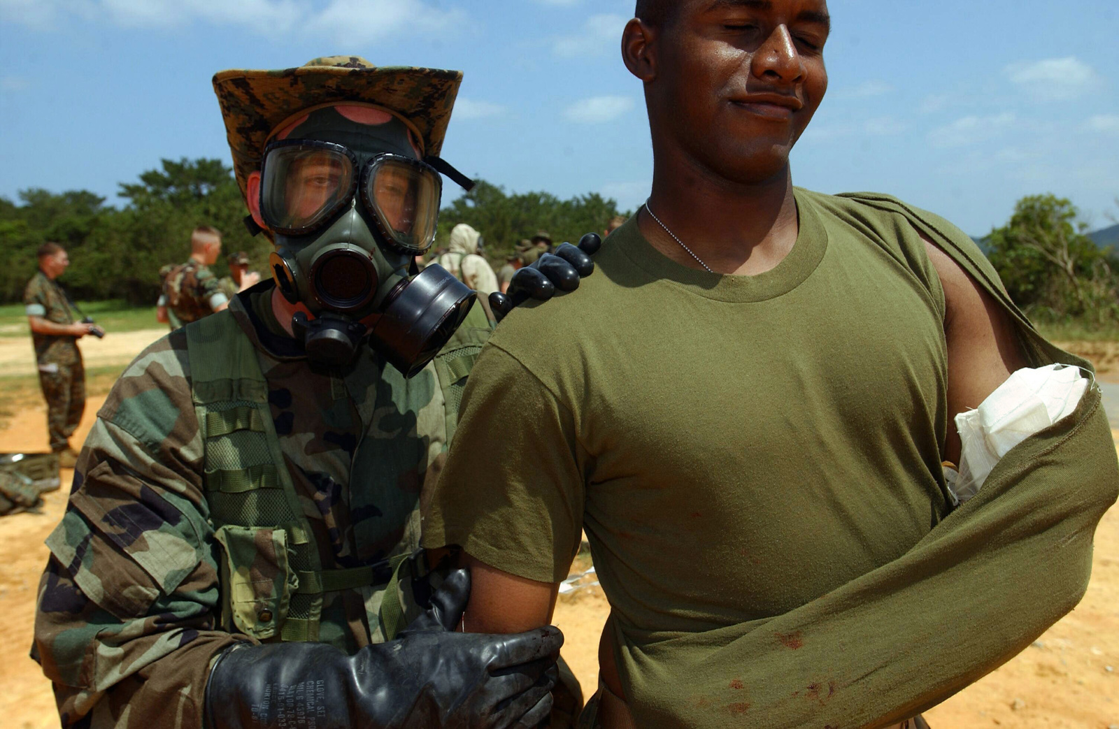 US Navy (USN) Hospital Apprentice (HA) Ian Stockwell (wearing gas mask), escorts US Marine Corps (USMC) Private First Class (PFC) Keith Taylor, 3rd Medical Battalion, to the triage area after treating him for an army injury, during a Nuclear, Biological, Chemical (NBC) mass casualty field training exercise, held at the Central Training Area, Okinawa, Japan