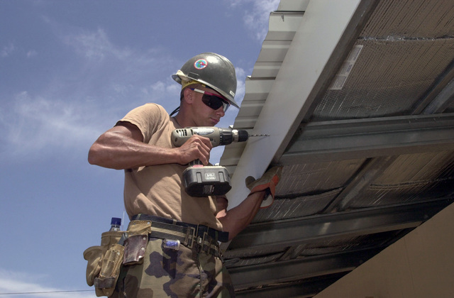 A U.S. Navy Builder Construction Man (BUCN) Jonathan Reaka, Naval Mobile Construction Battalion 133, Gulfport, Miss., drills a hole into a roofing support at a new school in Costanza, Domincan Republic, on April 29, 2003, during New Horizons 03. (U.S. Army photo by Kaye Richey) (Released)