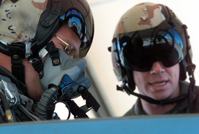 STAFF Sergeant (SSG) James Baxter, Headquarters and Headquarters Squadron (HHS), Marine Corps Air Station (MCAS) Yuma, Arizona, is being instructed by Major (MAJ) David Miner, a pilot with the Fixed Wing Training Fighter 401, just prior to a flight in an F5 Tiger II fighter jet