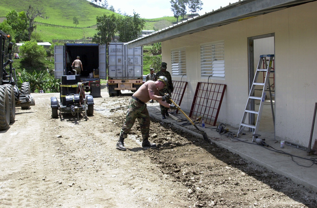 U.S. Navy Equipment Operator 2nd Class Scott Healy, Naval Mobile Construction Battalion 27, Brunswick, Maine, levels some dirt around a new school in Costanza, Dominican Republic, on April 29, 2003, during New Horizons 03. (U.S. Army photo by Miguel A. Negron) (Released)