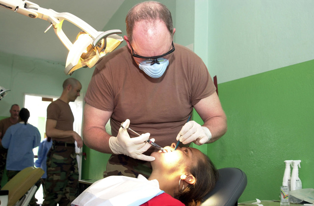 U.S. Army COL. Kevin Lords, Dentist, Utah Army National Guard (UTANG), extracts a tooth from a local woman during a Medical Readiness Training Exercise (MEDRETE) in Costanza, Dominican Republic, on April 30, 2003, during New Horizons 03. (U.S. Army photo by Miguel A. Negron) (Released)