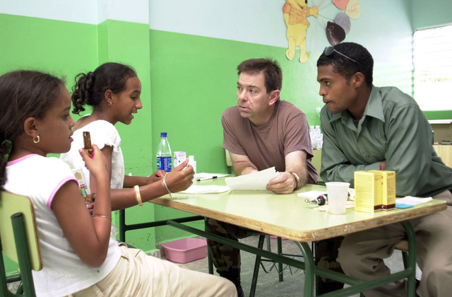 U.S. Army LT. COL. Peter Taillac (brown t-shirt), Utah Army National Guard (UTANG), listens to the medical problems of a young family during a a Medical Readiness Training Exercise (MEDRETE) in Costanza, Dominican Republic, on April 30, 2003, during New Horizons 03. (U.S. Army photo by Miguel A. Negron) (Released)
