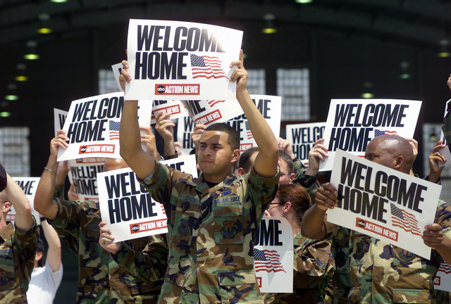 US Air Force (USAF) SENIOR AIRMAN (SRA) Juan Carlos Ochoa (foreground center) and other Airmen assigned to the 6th Operations Support Squadron (OSS), hold up welcome home signs provided by a local American Broadcasting Company (ABC) affiliate action news station, to show support for personnel arriving at MacDill Air Force Base (AFB), Florida (FL), following a deployment in support of Operation IRAQI FREEDOM