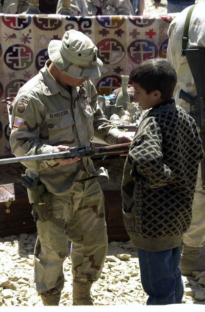 US Army (USA) MASTER Sergeant (MSG) Henderson, 82nd Airborne Division, barters with a local Afghani boy on the price of a souvenir rifle at the Bagram Bazaar on Bagram Air Field, Afghanistan, during Operation ENDURING FREEDOM. Local merchants are allowed one day a week (Fridays) to enter the military installation and sell their merchandise