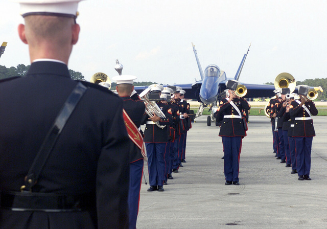 "The US Marine Corps (USMC) Band from the 2nd Marine Aircraft Wing, performs during a air show at Marine Corps Air Station (MCAS), Cherry Point, North Carolina (NC). A US Navy (USN) F/A-18 Hornet aircraft assigned to the USN ""Blue Angels"" Aerial Demonstration Team, is parked in the background"