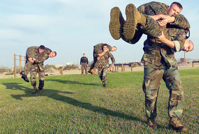 Marines carry fellow marine across Ramada Field as quickly as possible during a combat conditioning drill, which is part of the Marine Corps Martial Arts Program, Marine Corps Air Station (MCAS) Yuma, Arizona