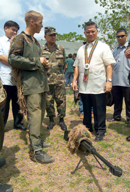US Marine Corps (USMC) Scout Sniper Sergeant (SGT) Corbin A. Robinson, left, with the 2nd Battalion, 7th Marines, describes the effectiveness of an M82A3 .50 Caliber Special Application Scope Rifle to Filipino dignitaries after participating in a demonstration of the interoperability with Filipino forces, during Exercise BALIKATAN 2003