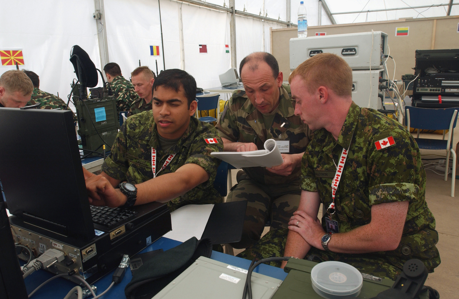 Multi-National Forces Soldiers work side-by-side configuring
