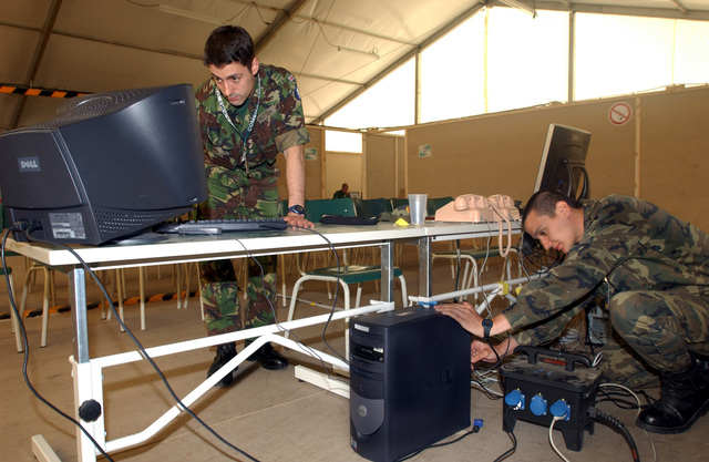 Royal Army (British) Captain (CPT) Alex Hutton (left), and Spanish Army Lieutenant (LT) Ignacio Ochoa, set up the computer system that will be used for slide presentations in the main theater room of the staging area during the US European Command (USEUCOM) -sponsored Exercise COMBINED ENDEAVOR, held at Lager Aulenbach, Germany. The Exercise is a Partnership for Peace (PfP) exercised hosted by Germany, and is the largest information and communications systems exercise in the world which focuses primarily on Command, Control, Communications, and Computers (C4) interoperability testing and documentation