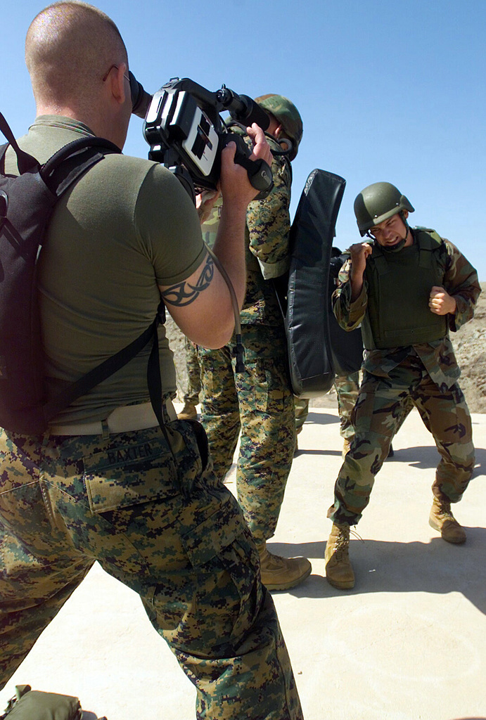 STAFF Sergeant (SSG) James Baxter, Combat Visual Information Center (CVIC), Marine Corps Air Station (MCAS) Yuma, Arizona, films SSG Nicholas Hillebrand, from Headquarters and Headquarters Squadron (H&HS), performing rear hand punches during a Marine Corps Martial Arts Program combat conditioning drill