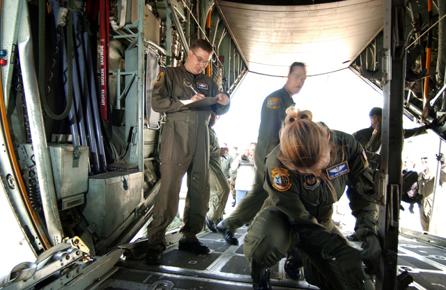 US Air Force (USAF) Technical Sergeant (TSGT) Craig Larsen, Non-Commissioned Officer In Charge (NCOIC) of Standards and Evaluation, 86th Aeromedical Evacuation Squadron (AES), watches closely as Lee Ann Rickard, an In-Flight Nurse with the 86th AES, works to reconfigure the cargo compartment of a USAF C-130 Hercules aircraft for medical evacuation, during a training competition held for Nurse/Technician appreciation week, at Ramstein Air Base (AB), Germany