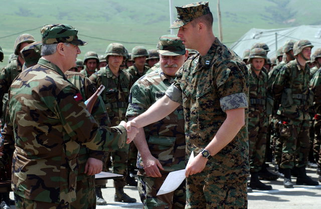 An unidentified Republic of Georgia Army STAFF Officer (left), assigned to the 16th Mountain Battalion, presents US Marine Corps (USMC) Captain (CPT) Mark Carter, Task Force Georgia Train and Equip Program (GTEP), with a token of appreciation from the Georgian Minister of Defense, during a Certification Ceremony, held at the Krtsanisi Training Area, at Rock City, Georgia. The ceremony marks the completion of the third tactical training phase for Soldiers participating in the program. GETEP is a phased training initiative that enhances operational capabilities of select Georgian units to increase security of Georgia's borders and promote stability within the region