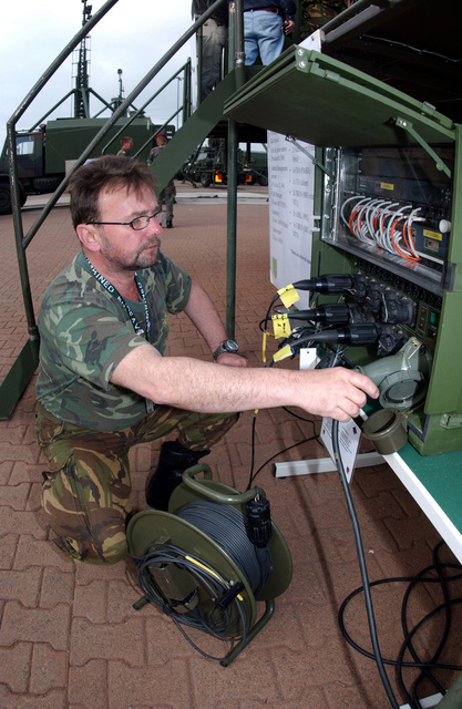 Belgium Army First Sergeant Major (1SGM) Patrick Costanza, Broadband Integrated Command Post Communications Network (BIGSTAF) Operator, tests connectivity between a phone line and a fax machine at Lager Aulenbach, Germany, during Exercise COMBINED ENDEAVOR 2003. The Exercise is a Partnership for Peace (PfP) exercised hosted by Germany, and is the largest information and communications systems exercise in the world which focuses primarily on Command, Controls, Communications, and Computers (C4), interoperability testing and documentation